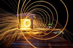 Scintille dorate calde che volano dall'uomo che fila lana d'acciaio bruciante sopra Fotografia Stock