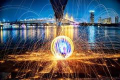Scintille dorate calde che volano dall'uomo che fila l'ONU bruciante della lana d'acciaio Fotografia Stock