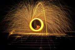 Scintille dorate calde che volano dalla bruciatura di filatura dell'uomo Immagini Stock