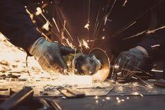 Scintille fatte utilizzando uno strumento circolare della macinazione su una superficie di metallo in un'officina Fotografia Stock Libera da Diritti