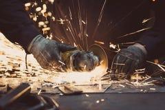 Scintille fatte utilizzando uno strumento circolare della macinazione su una superficie di metallo in un'officina Fotografie Stock Libere da Diritti