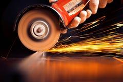 Scintille roventi al materiale dell'acciaio della macinazione Fotografie Stock Libere da Diritti