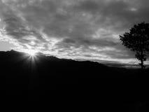 Scintillement du soleil derrière la montagne Image libre de droits
