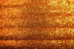 Scintillio dorato rosso - macro di una sfera di natale Immagine Stock