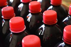 Sciroppi di frutta rosso scuro in bottiglie di plastica con i coperchi rossi fotografia stock
