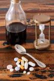 Sciroppo in bottiglia di vetro, pillole e clessidra d'annata Fotografia Stock Libera da Diritti
