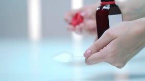 Sciroppo di versamento della medicina della mano femminile dalla bottiglia Prevenzione di influenza Ritardi e braccia stock footage