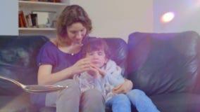 Sciroppo di versamento di tosse di medico in un cucchiaio sui precedenti di una madre con un bambino malato e febbricitante video d archivio