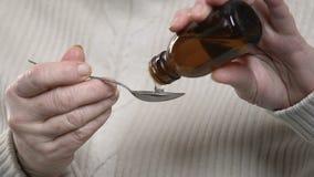 Sciroppo di versamento invecchiato malato di tosse di signora in cucchiaio con le mani vacillante, ritenenti indisposte stock footage