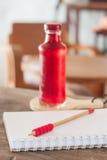 Sciroppo rosso nella bottiglia sul piatto di legno immagini stock libere da diritti