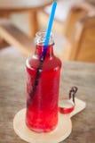 Sciroppo rosso nella bottiglia sul piatto di legno Immagine Stock Libera da Diritti