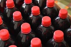 Sciroppo rosso scuro della frutta in bottiglie di plastica fotografie stock