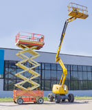 Scissor and articulated boom wheeled lifts on asphalt ground. Wheeled scissor lift and wheeled articulated lift with telescoping boom and basket on an asphalt Stock Photo