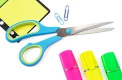 Scissor, Büroklammer, Stikers und drei Leuchtmarker-Stifte auf Weiß Stockfotografie