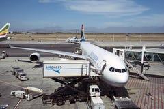 Scissor el camión de la elevación y del abastecimiento junto a un avión de pasajeros Imagen de archivo libre de regalías