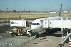 Scissor el camión de la elevación y del abastecimiento junto a un avión de pasajeros Fotografía de archivo