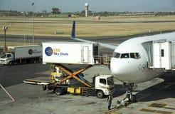 Scissor el camión de la elevación y del abastecimiento junto a un avión de pasajeros Foto de archivo libre de regalías