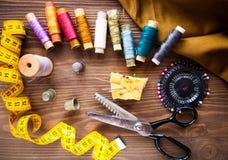 Scissor, knappar, vinandet, måttbandet, tråden och fingerborg på fabri Royaltyfri Fotografi