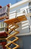Scissor la plataforma de la elevación para la reparación de la fachada de una casa Fotos de archivo libres de regalías