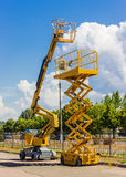 Scissor lift and articulated boom lift. Two types of mobile aerial work platform - yellow scissor hydraulic lift and yellow hydraulic articulated boom lift Royalty Free Stock Images