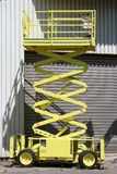 Scissor lift. Extended scissor lift in front of industrial building Stock Photo