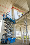 Scissor lift platform on a construction site. Workers are high up in cherry picker on building site Stock Photos