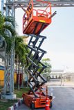 Scissor lift platform and electrical technician operated wiring. Construction field Stock Photos