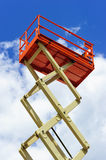 Scissor lift platform. With hydraulic system at maximum height range painted in orange and beige colors, large construction machine, heavy industry, white Stock Photos