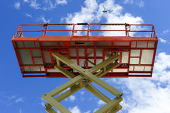 Scissor lift platform. With hydraulic system at maximum height range painted in orange and beige colors, large construction machine, heavy industry, white Stock Images