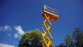 Scissor lift platform. With hydraulic system at maximum height range painted in orange colors, large construction machine, heavy industry, white clouds and blue stock photos