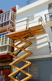 Scissor lift platform for repair of the facade of a house Royalty Free Stock Photos
