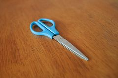 Scissor mit blauem Griff auf Holztischhintergrund stockfotografie