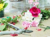 Scissor på tabellen av blommaordningen Fotografering för Bildbyråer
