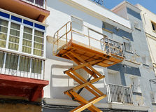 Scissor a plataforma do elevador para pintar da fachada de uma casa imagens de stock