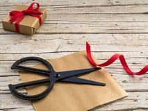 Scissor, presente e fita vermelha no fundo de madeira fotografia de stock