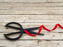 Scissor and red ribbon on wooden background Stock Images