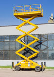 Scissor self propelled lift on the background of industrial buil. Mobile aerial work platform - yellow scissor hydraulic self propelled lift against the backdrop Stock Photos