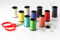 Scissor and Sewing threads multicolored background closeup.  Royalty Free Stock Image