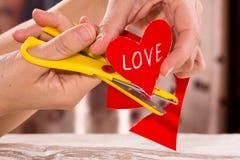 Scissoring le coeur de papier pour la Saint-Valentin Photographie stock libre de droits