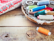 Scissors, bobbins with thread and needles, striped fabric. Old sewing tools on the old wooden background. Stock Image