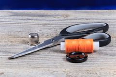 Scissors, button, spool of thread. And a needle on the table Stock Photo