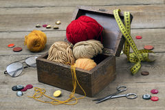 Scissors, buttons, yarn, glasses. On a wooden table Stock Photo