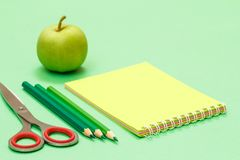 Scissors, color pencils, notebook and apple on the green background. Back to school concept. School supplies. Shallow depth of field royalty free stock image