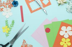 Scissors, colored paper, cut out shapes and flowers royalty free stock photo