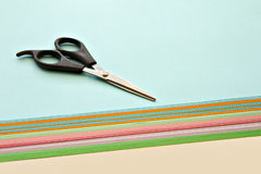 Scissors and colored papers. Black scissors lying on a stack of colored papers Stock Photos