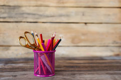 Scissors and colorful pencils of violet yellow pink red and orange in stationary cup on wooden table and background. Copyspace Stock Photos