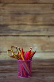 Scissors and colorful pencils of violet yellow pink red and orange in stationary cup on wooden table and background Stock Photos