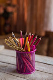 Scissors and colorful pencils of violet yellow pink red and orange in stationary cup on wooden table and background Stock Photo