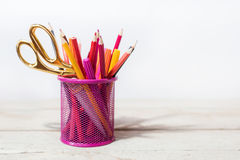 Scissors and colorful pencils of violet yellow pink red and orange in stationary cup on wooden table and white background Stock Photos