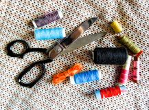 Scissors and colorful sewing threads royalty free stock photos